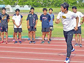 参加者に速く走るこつを指導する朝原さん(右)