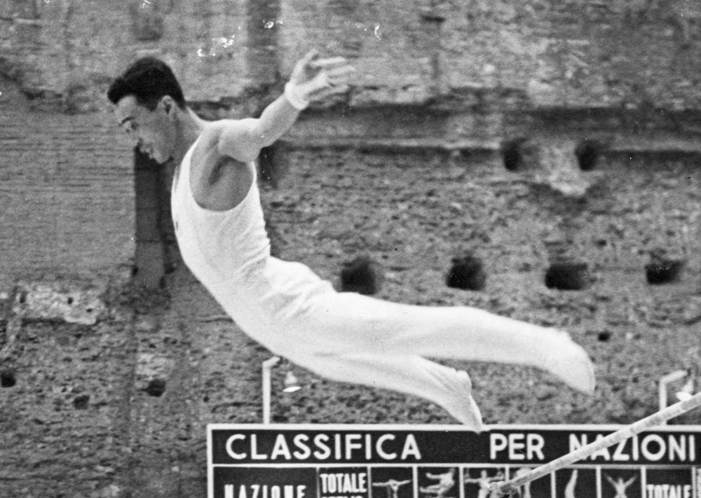 1960年ローマ五輪の体操は古代ローマ時代のカラカラ浴場跡で開催された。遺跡の壁をバックに、鉄棒でフィニッシュに入る相原信行(UPI=共同)