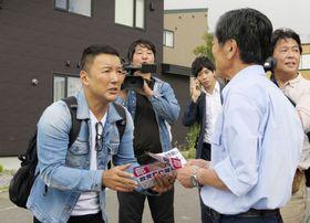 住民と握手するれいわ新選組の山本代表(左)=18日午後、北海道利尻富士町