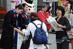 通行人に青森県観光をPRする(左から)塩田さん、佐藤さん=18日、東京・飯田橋