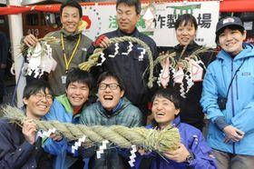 完成したしめ縄を手に笑顔の第61次南極観測隊員=14日、南極海(共同)