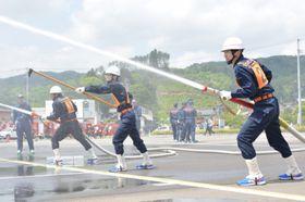 機敏な動きで自動車ポンプ操法を披露する滝沢市消防団員