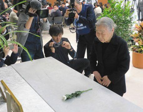 献花台に花をささげる宮沢節子さん=16日、東京都世田谷区で