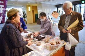 菓子を品定めする買い物客=鹿児島市の県市町村自治会館