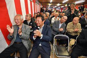 板柳町長選で成田さんの再選が決まり、拍手で喜びを表す支持者ら=午後9時59分
