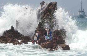 高波のため岩場に孤立し、救助される海水浴客=18日午後、福井県美浜町(敦賀海上保安部提供)