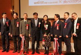 発表会見で記念撮影に応じる澤田社長(中央左)、CCTVMALLの肖飛総裁(右から2人目)ら=佐世保市、ハウステンボス