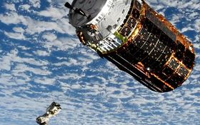 国際宇宙ステーションに近づく無人補給機「こうのとり」9号機。左下はステーションから伸びるロボットアーム(NASAテレビから)