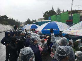 降りしきる雨の中、新基地建設に抗議し座り込みをする市民ら=14日、名護市辺野古の米軍キャンプ・シュワブゲート前