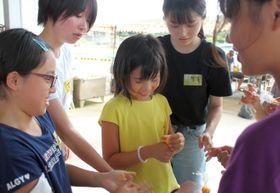 バスボム作りを楽しむ子どもたちと学生=佐世保市、高島