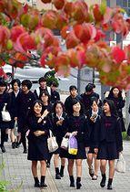 木々の葉が色づく中、冬服に衣替えして登校する岩手女子高の生徒=2日、盛岡市大沢川原