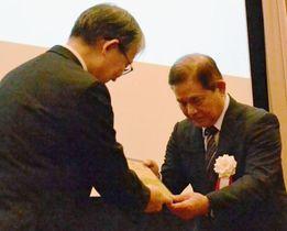 山口寿一会長(左)から記念盾を受け取る知花朝盛さん=21日、東京都千代田区