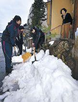 高齢者宅の軒先で雪かきに励む生徒=金沢市末町