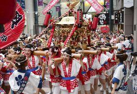 「ギャルみこし」を担ぎ、商店街を練り歩く女性たち=23日午前、大阪市