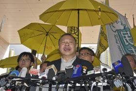 開廷前に香港の裁判所敷地内で心境を語る戴耀廷氏=24日(共同)