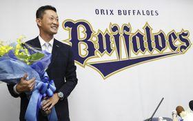 引退表明の記者会見を終え、花束を手に笑顔を見せるオリックスの岸田護投手=20日、京セラドーム