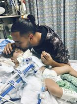 アブドラ・ハサンちゃん(左)と父親=米カリフォルニア州オークランドの病院(米イスラム関係評議会サクラメント・バレー提供、共同)