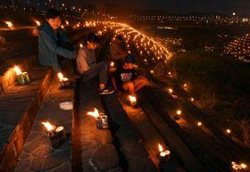 たいまつの明かりが照らす幻想的な雰囲気を楽しむ来場者=日置市吹上町永吉