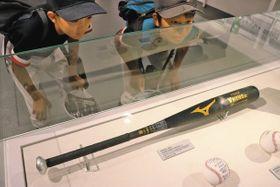 サイクル安打を達成した杉田選手のバットに見入る子どもたち=兵庫県西宮市の甲子園歴史館で