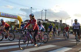 一斉にスタートする本島一周サイクリングなどの参加者=9日午前7時すぎ、名護市・21世紀の森体育館前