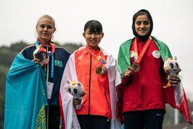 陸上のアジア・ユース選手権、女子2000m障害で優勝し、笑顔でメダルを掲げる村上弓月(中央)=15日、香港(ゲッティ=共同)
