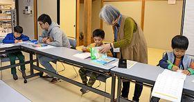 大学生や地域住民に教わりながら勉強する子どもたち