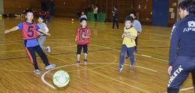 ヴァンラーレの選手(右)とともにサッカーゲームを楽しむ児童