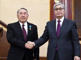 握手するカザフスタンのトカエフ新大統領(右)とナザルバエフ前大統領=20日、アスタナ(ロイター=共同)