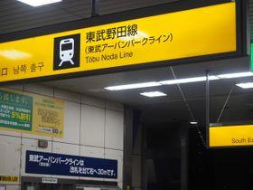 手前(黄色)と奥(紺色)で案内板の路線名が主従逆転=JR柏駅の改札口