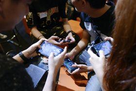 タイ・バンコクのイベントで携帯電話のゲームをする人たち=2017年12月(ゲッティ=共同)