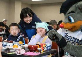 球団マスコット「B・B」と食事を楽しむ子どもたちと、支援活動を発案した田中さん(左奥)=金田翔撮影