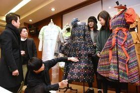 完成した衣装を確認する学生ら=神戸市中央区国香通6
