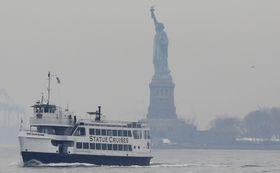 自由の女神像やエリス島へのツアー船=22日、ニューヨーク(AP=共同)