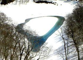 雪解けに伴いドーナツ状に沼面が現れた石沼