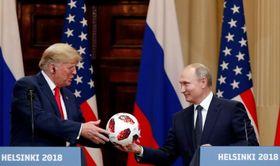 16日、フィンランド・ヘルシンキでの首脳会談後の共同記者会見で、ロシアのプーチン大統領からサッカーボールを受け取るトランプ米大統領(ロイター=共同)