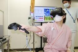 仮想現実(VR)を使った装置「カグラ」で脳梗塞後のリハビリをする女性=9月、兵庫県西宮市の兵庫医大病院