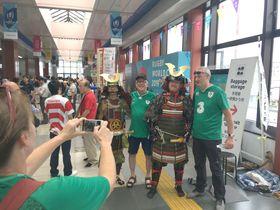 甲冑を試着し、記念撮影するアイルランドチームのファンら =横浜市港北区のJR小机駅構内