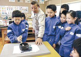 「火のし」を使って布のしわを伸ばす児童=加賀市南郷小