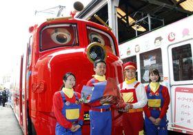 英国の人気鉄道アニメ「チャギントン」のキャラクターをあしらった路面電車の前で写真に納まるタレントのつるの剛士さん(右から2人目)ら=16日午前、岡山市