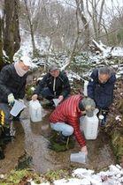 「立春大吉」の仕込みに使う水をくむ佐渡北雪会のメンバーら=21日、佐渡市赤泊地区
