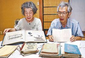 正雄さんが残した日記や当時の写真を手に、正雄さんへの思いを語る洋子さん(左)と和夫さん=高岡市内の洋子さん宅