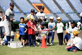 うまく打つためのこつを野球部員から教わる児童=倉敷マスカット