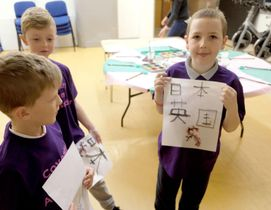 16日、英中部コベントリーで開かれた日本文化紹介イベントで、自分で書いた習字の作品を見せる児童(共同)