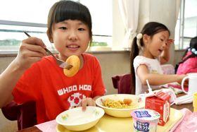 ロシアの伝統料理「ピロシキ」を口に運ぶ子どもたち=海老名市中新田