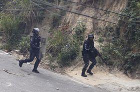 ベネズエラ首都カラカス周辺での兵士らの反乱に呼応して起きた反政府デモの参加者を追い払おうとする警官=21日(AP=共同)