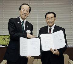 協定書に調印した後、握手する港区の武井区長(左)と平川市の長尾市長=25日、東京・港区役所