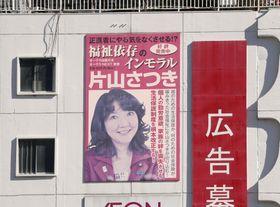 名古屋市のビル壁面に設置された片山地方創生相の書籍の広告看板=20日午前