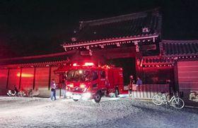 京都御所の門を出る消防車両=23日午後9時51分、京都市