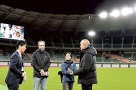 県担当者(左)と一緒に照明の照度を確認する組織委員会関係者ら=11日夜、袋井市のエコパスタジアム