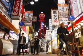 新型コロナウイルス対策で警戒度が「赤信号」に引き上げられてから初の週末を迎えた大阪・新世界。中央奥は赤く点灯した通天閣=5日午後5時37分